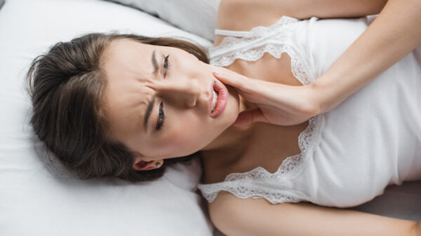 woman suffering from tooth pain while lying in bed